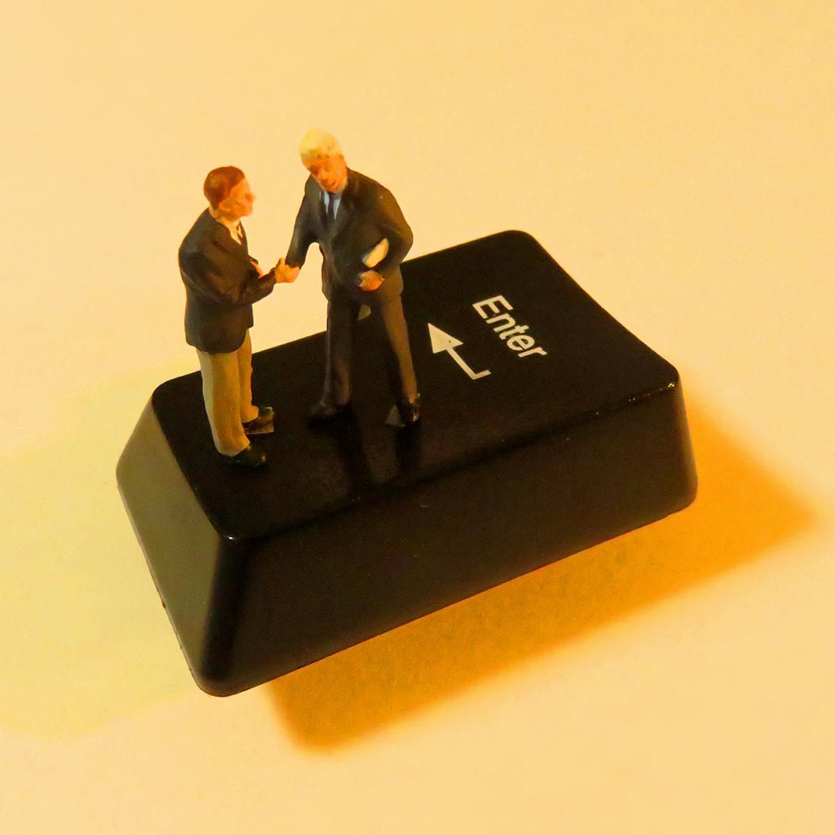 Enterキーで契約が成立して握手を交わすビジネスマン