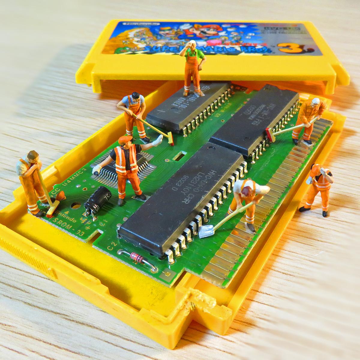 7月15日はファミコンの日!ファミコンのカセットを分解してキレイに掃除する作業員