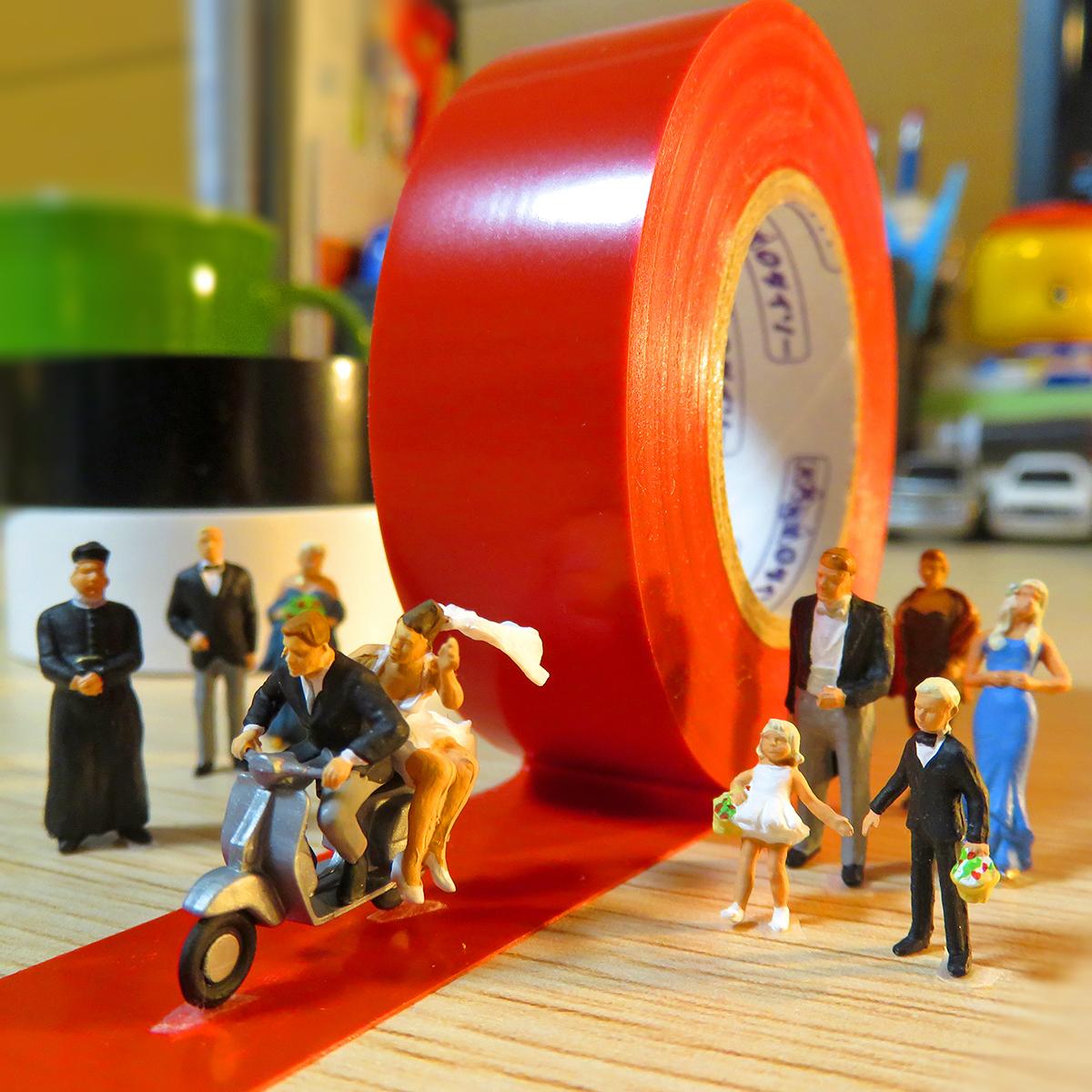 赤テープのバージンロードをバイク走行するウェディングカップル