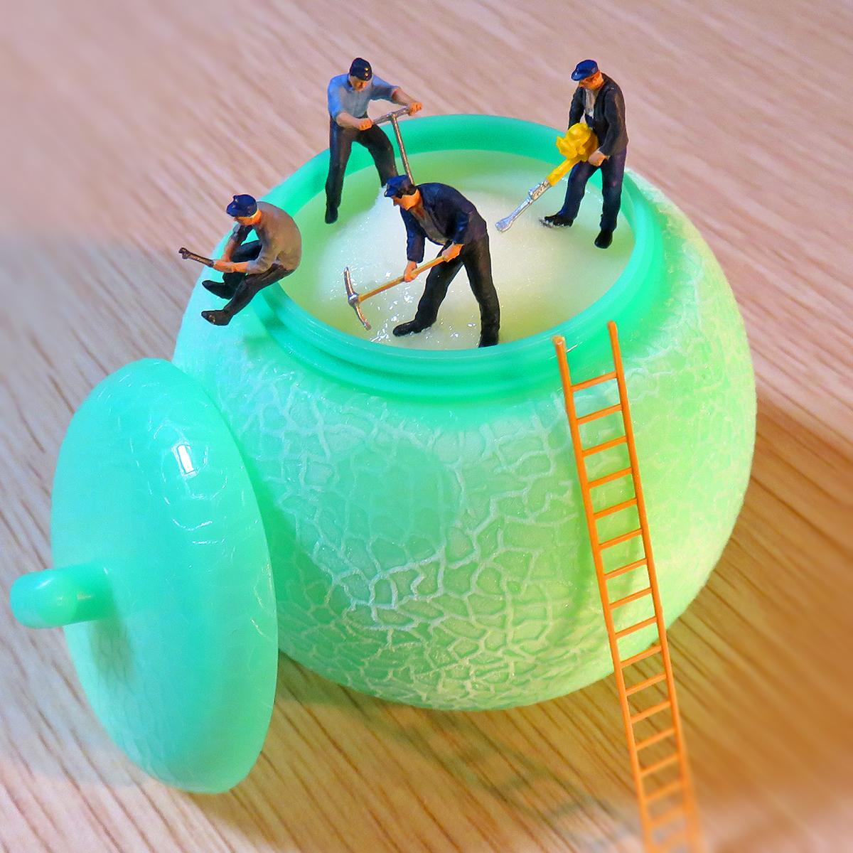 固まったメロンアイスを掘る作業員
