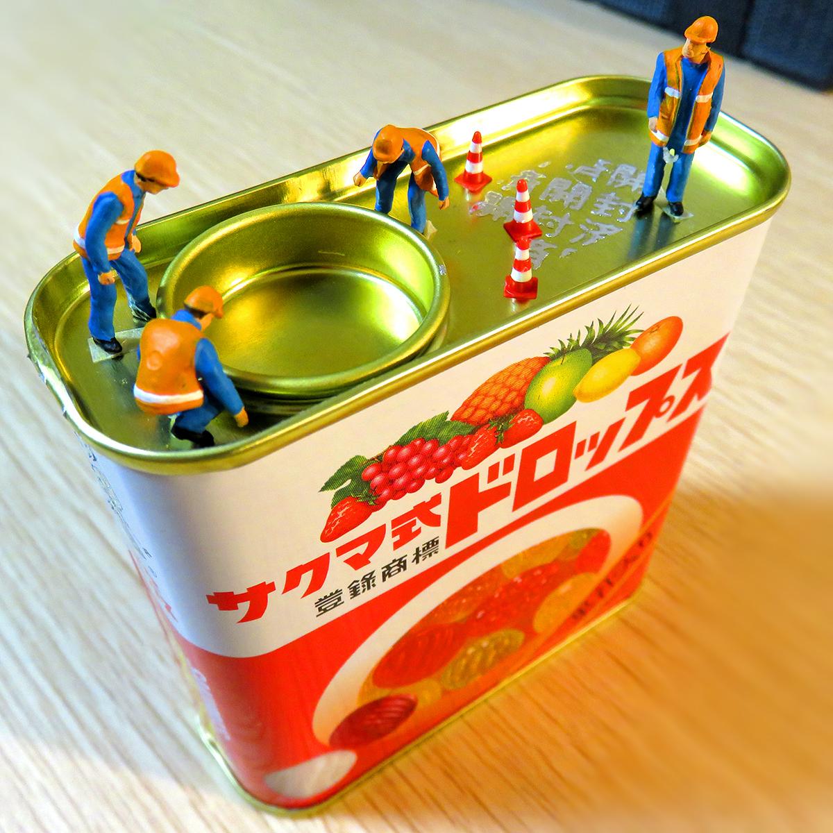 サクマ式ドロップスの缶が開かなくて困ってる作業員たち