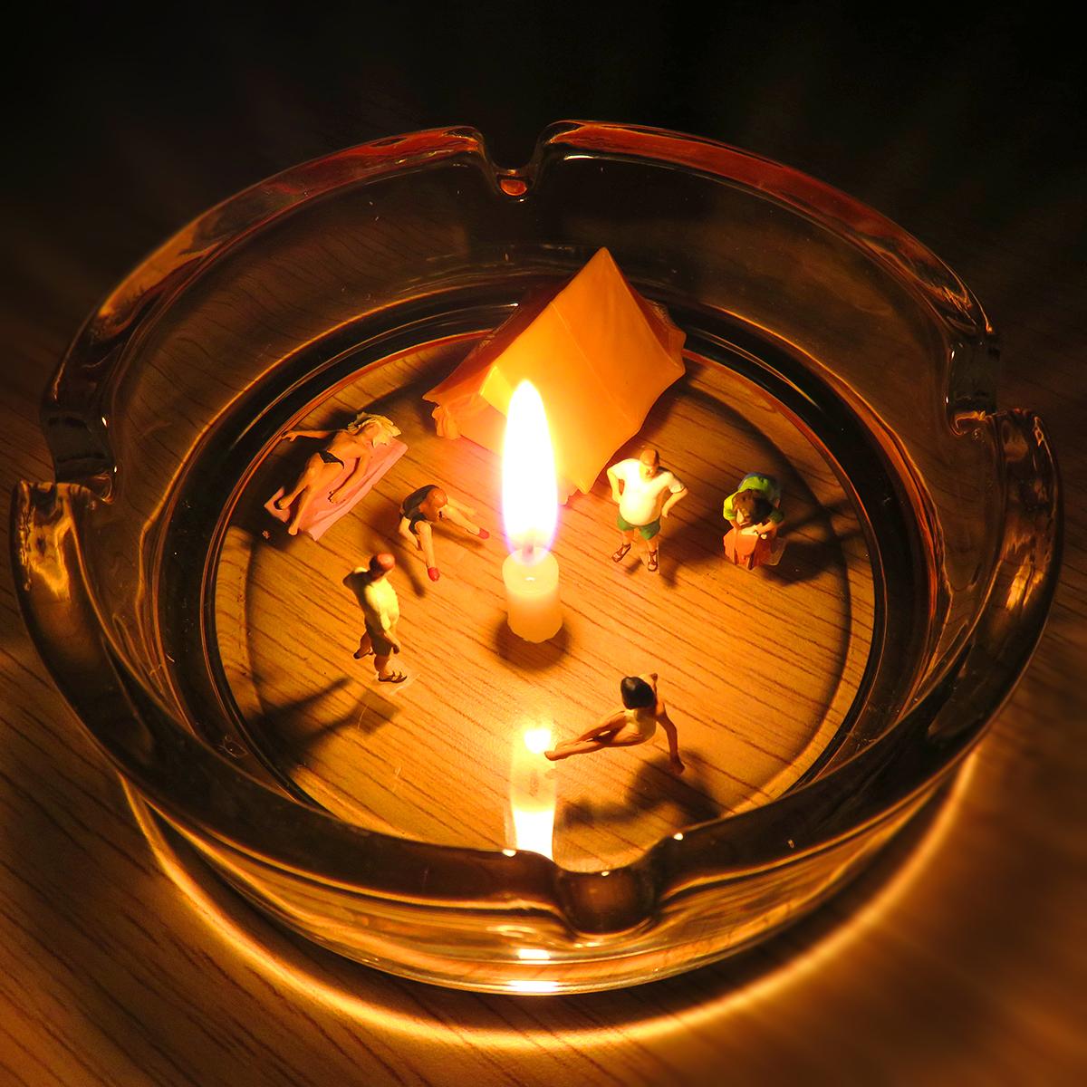灰皿にテントを立てて蝋燭の火を灯してキャンプする若者たち