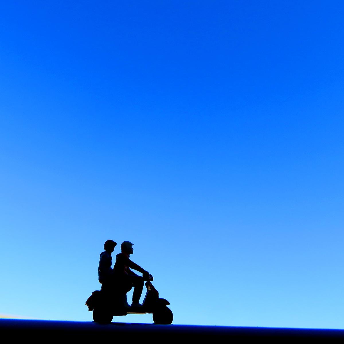 雲ひとつない青空の下でバイク2人乗りするカップル