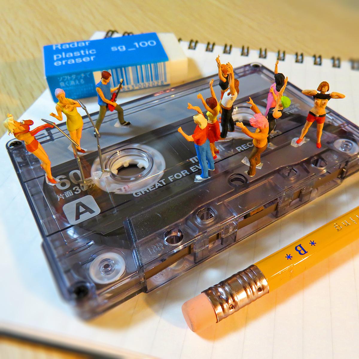 カセットテープでライブする音楽アーティストと盛り上がる観客たち