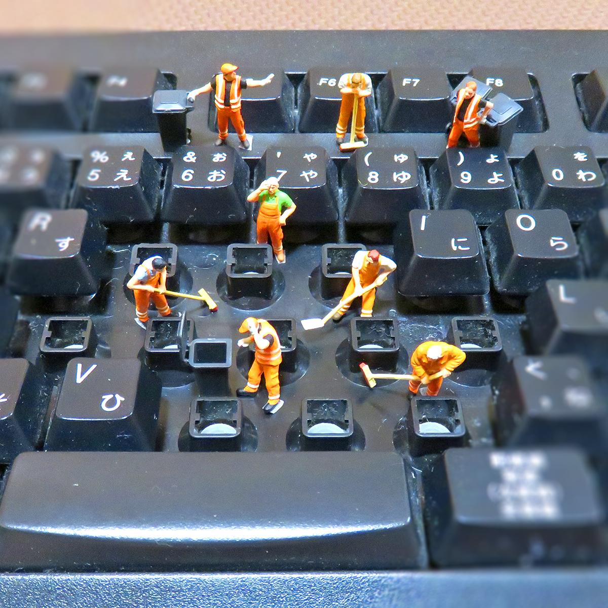 キーボードのキーを外して掃除する清掃員たち