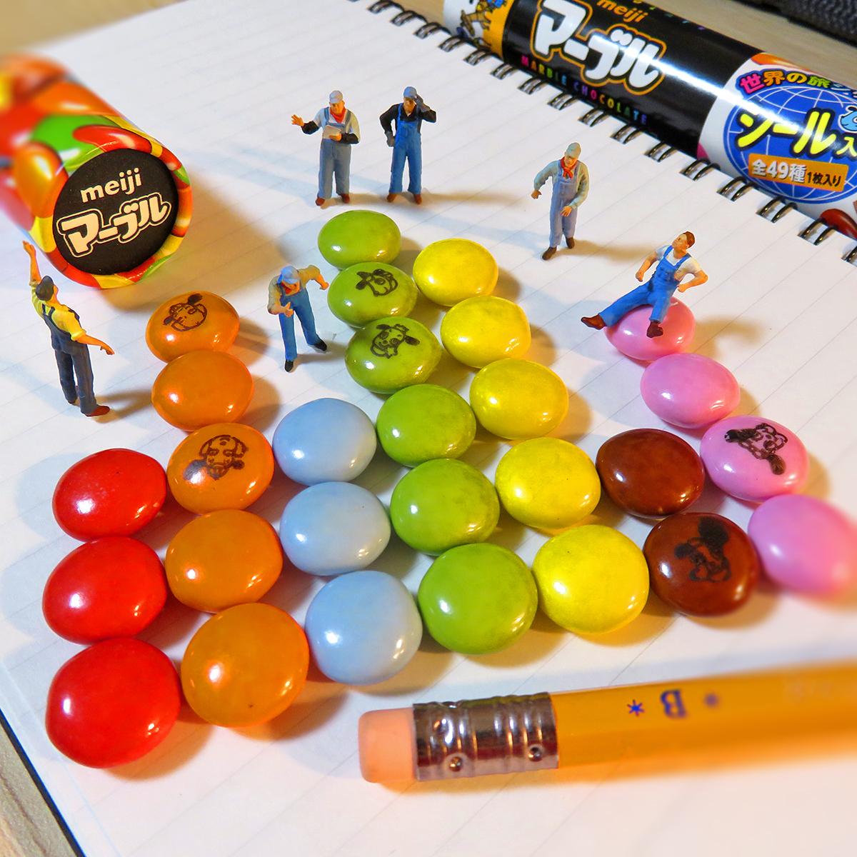 明治マーブルチョコを色別に整理する作業員たち