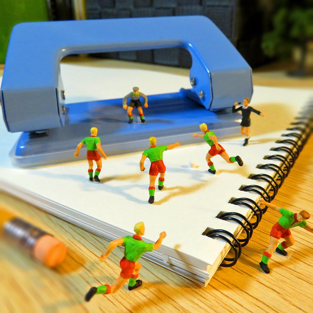 穴あけパンチのゴールポストでサッカーするサッカー選手たち